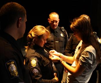 Police receiving pin as part of Forest City Times project